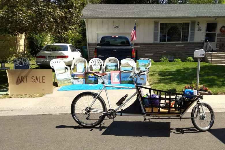 A cargo bike in front of an art sale.