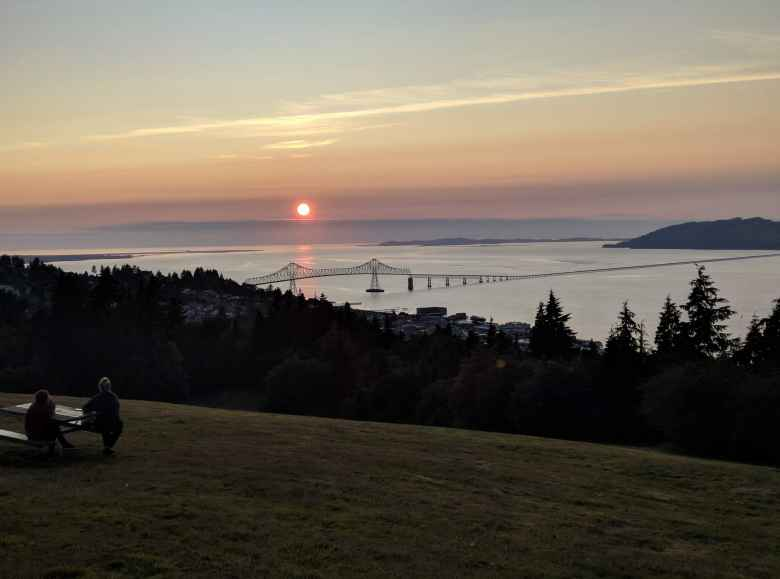 Then sun setting over the Pacific Ocean west of the US-101 bridge connecting Astoria, Oregon to Chinook, Washington.