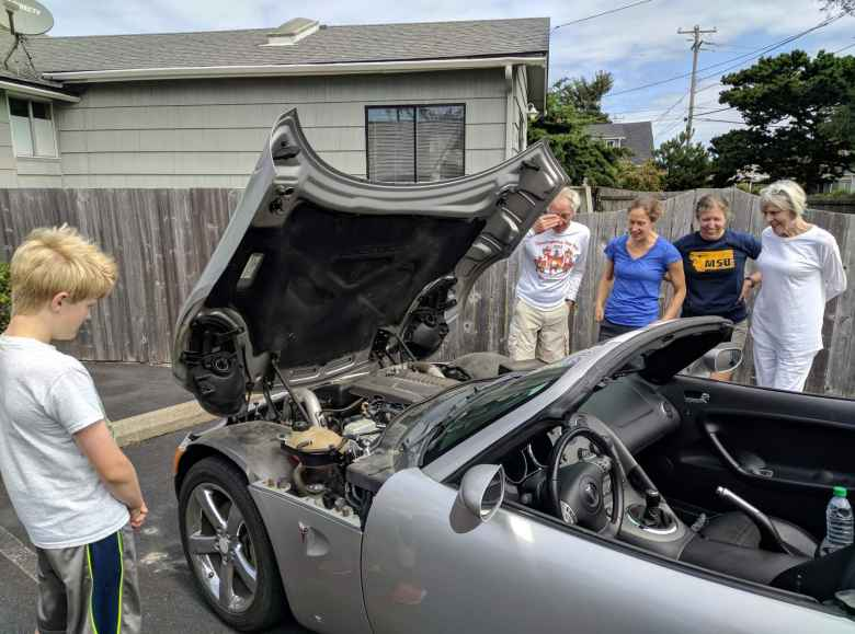 people looking at engine of silver Pontiac Solstice GXP with hood open
