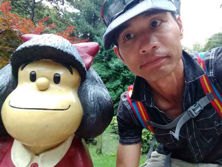 Felix Wong with the statue of Mafalda (an Argentine comic character) in the park Campo de San Francisco.