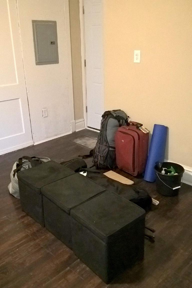 backpack, red suitcase, blue yoga mat, bucket, three black ottomans