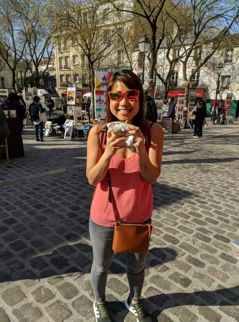 Angie with a crepe in front of Place de Tertre in Montmartre.