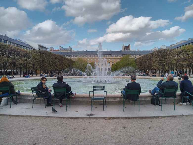 People relaxing around the fountain at the Palais-Royal.