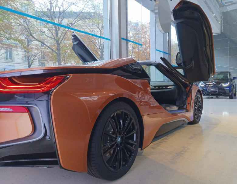 An orange BMW i8 inside the BMW showroom at George V. A dark blue BMW i3 is in the background.