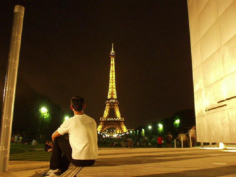 Felix Wong admiring the night view of the lighted Eiffel Tower from L'Parc du Champ de Mars.