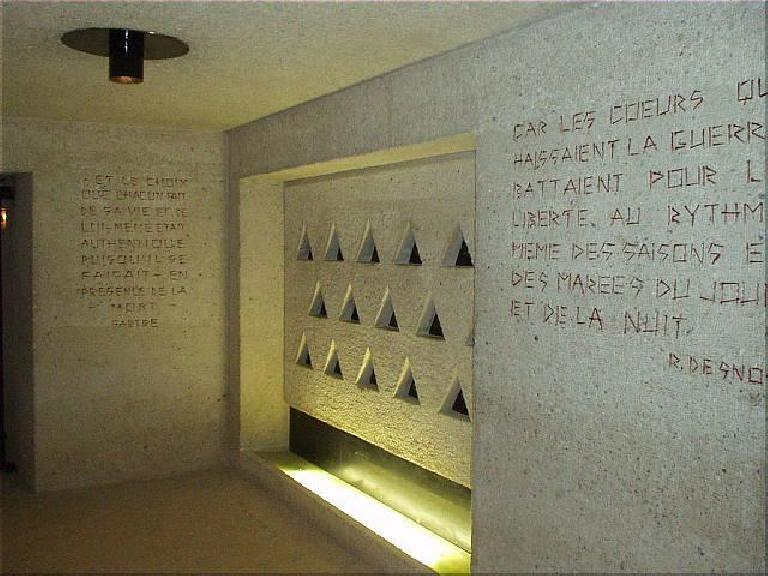 "The triangles are representative of the identification patches inmates were forced to wear.  Just to the right of this, above the exit, are the words, ""Pardonne, n'oublie pas..."" (""Forgive, don't forget..."") (August 17, 2003)"