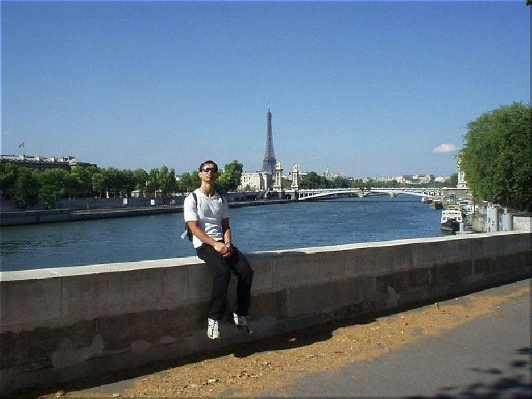 Everywhere you look there are architectural masterpieces all over Paris!  Here's Felix Wong with L'Tour Eiffel in the distance. (August 17, 2003)