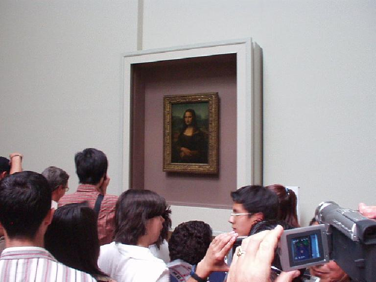 [Louvre] At last, I see the Mona Lisa!!  Note the huge crowd around it, including many people who seemed to walk right by the other exhibits without giving so much as a glance.  It is a great painting, though, exuding both beauty and intrigue.