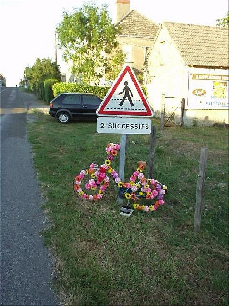[KM 1070, 70:06 elapsed, 8:06pm] I saw many displays like this... bicycles covered with flowers in support of the PBP riders. (August 21, 2003)