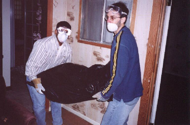 "Here's fellow ""Destroyers"" Sam and Patrick taking out a bag of sheetrock, which used to be part of the ceiling!"