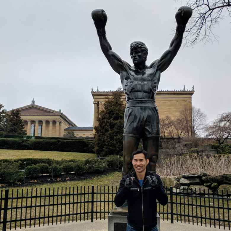 Felix Wong poses as a boxer in front of the Rocky Balboa statue.