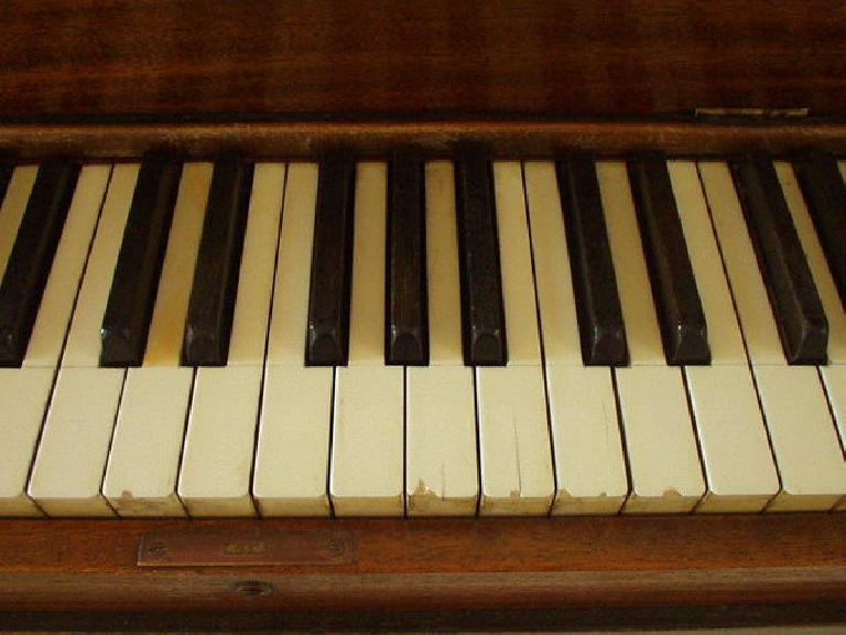 """After I tuned the piano (several hours), I turned my attention to aesthetics.  Here is a """"before"""" shot of the chipped and faded keytops."""