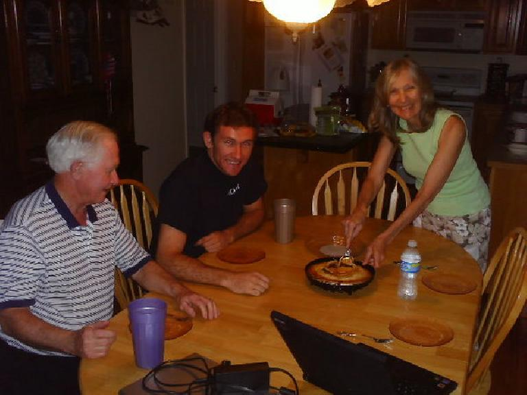 Dick Vail, Tim Vail, Dee Vail at a kitchen table with Dee cutting some apple pie