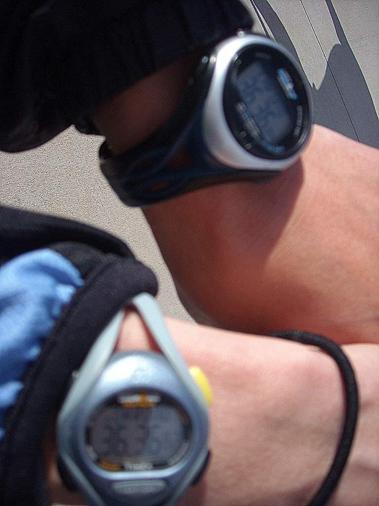 Timex Ironman watches on two different runners' wrists, one with a time of 36:36.82 and the other with 36:36.84.