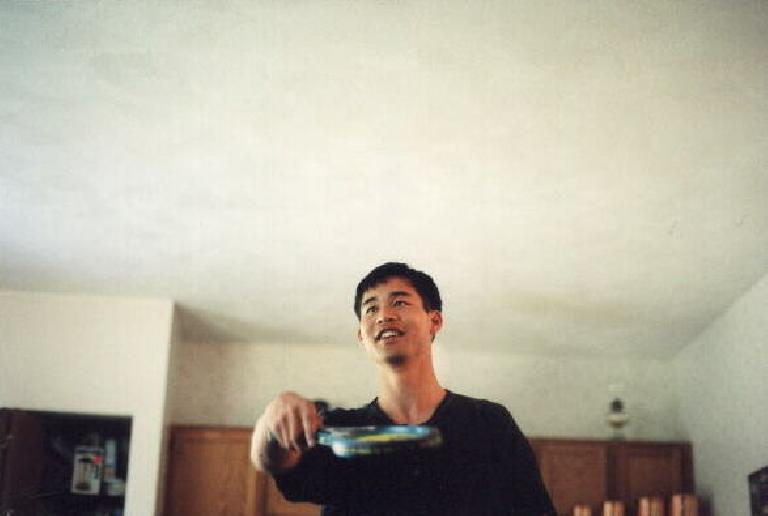 Felix Wong playing with Maxine's virtual tennis racket.  If I remember correctly, I won. (July 18, 1999)