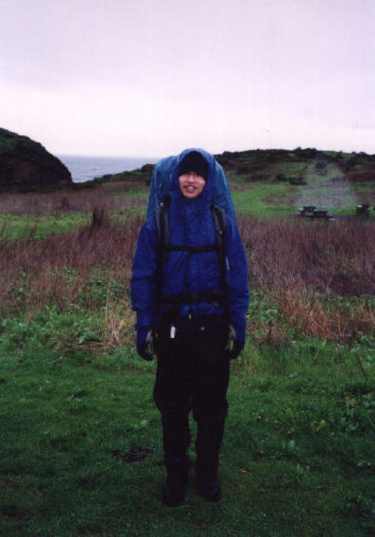 Felix Wong all donned up in rain gear, ready to start a new day.  Now if only it would rain! (February 19, 2001)