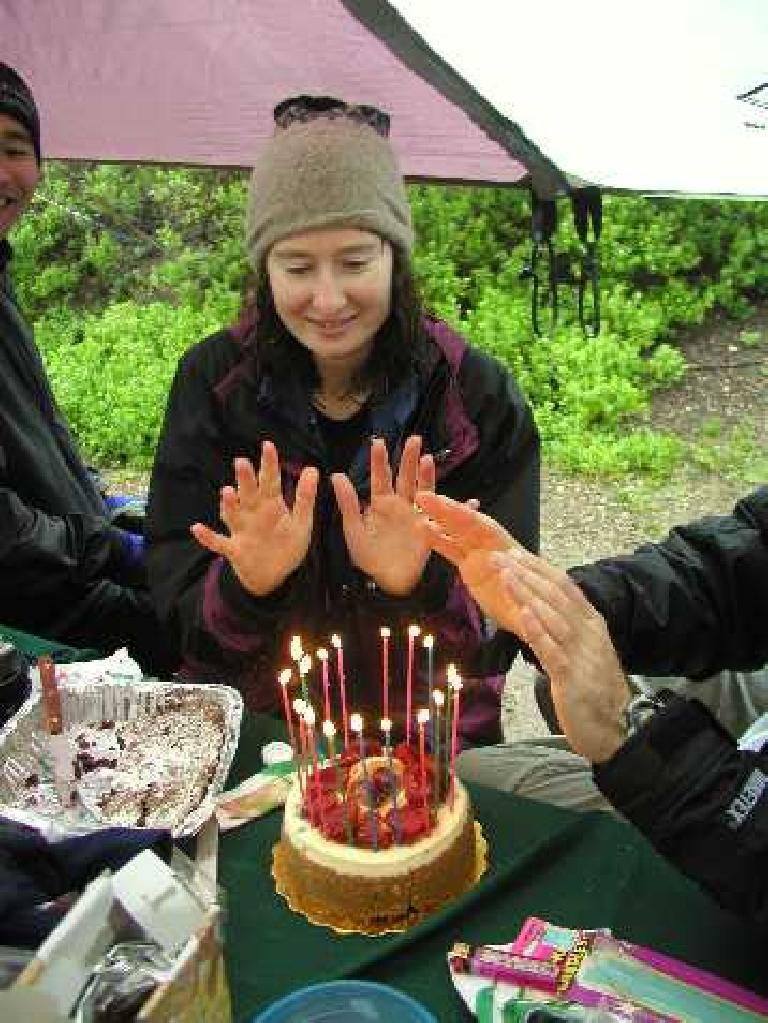 Kathleen and others warming up their hands over the birthday cake! Photo: Adrian Mikolajczak.