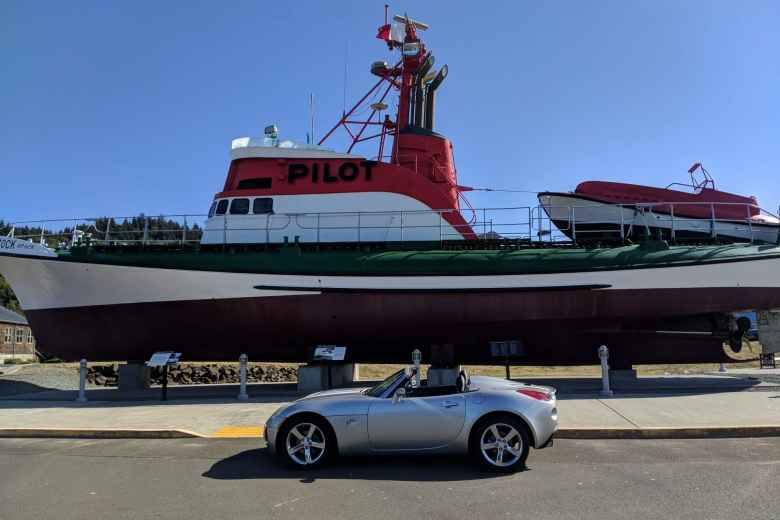 Silver Pontiac Solstice GXP in front of a Pilot ship in Astoria, Oregon.