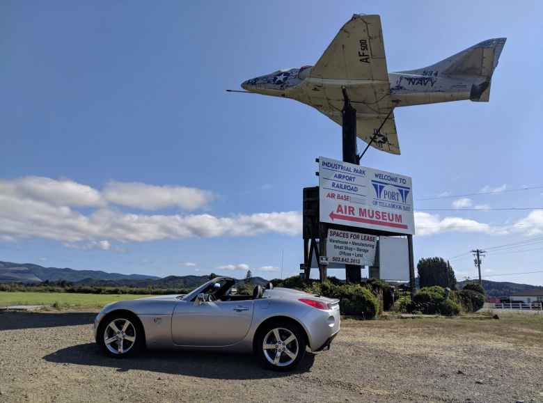 Silver Pontiac Solstice GXP in front of a Navy jet at the Tillamook Air Museum.