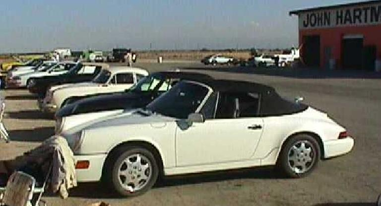 white 1990 Porsche 911 Carrera Cabriolet with black top and a row of Porsches next to it on an airport base
