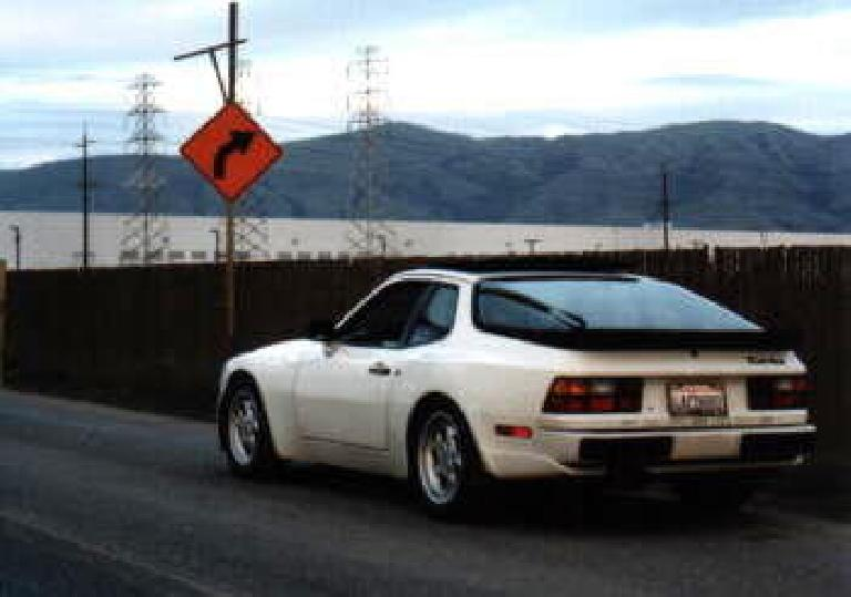 Right view view of white 1986 Porsche 944 Turbo in front of an orange turn right sign.