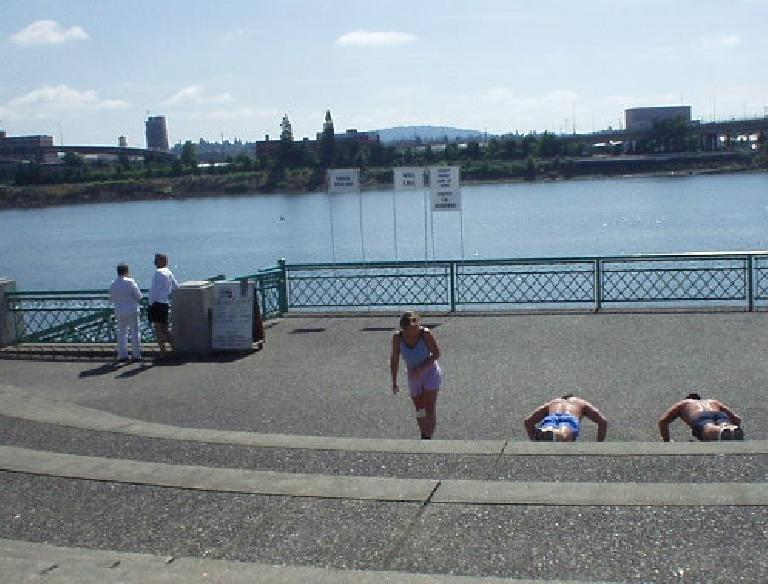 Underscoring that this is a fit city, here are some guys doing pushups while a good-looking woman walks on by.