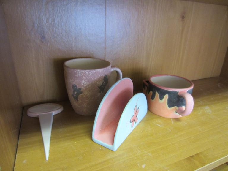 Tori's garden stake and flying cats mug; Raquel's napkin holder; and my tea cup before glazing.