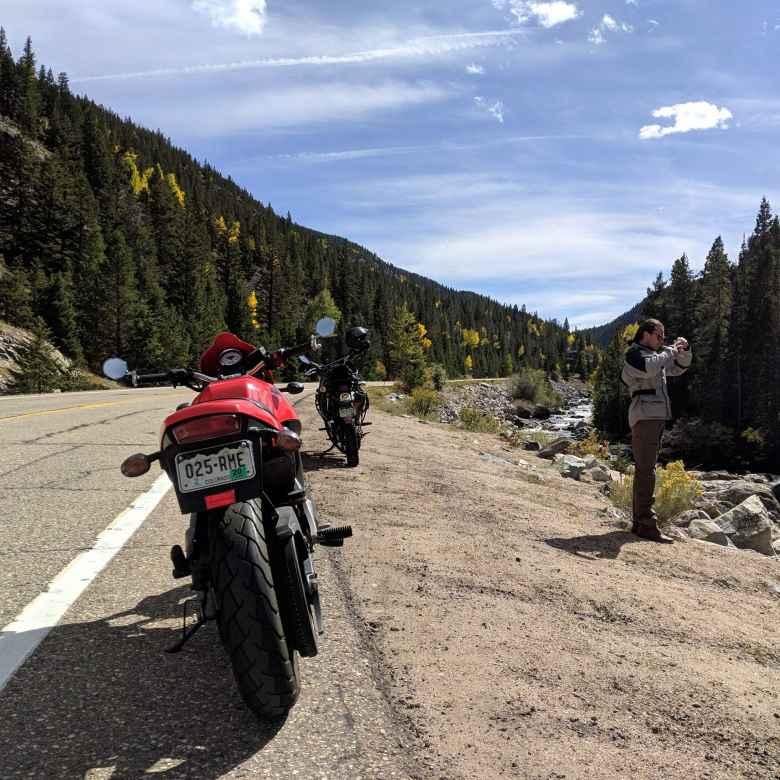 red 2003 Buell Blast, black Kawasaki KLR rear view, Alex taking a photo, Poudre Canyon