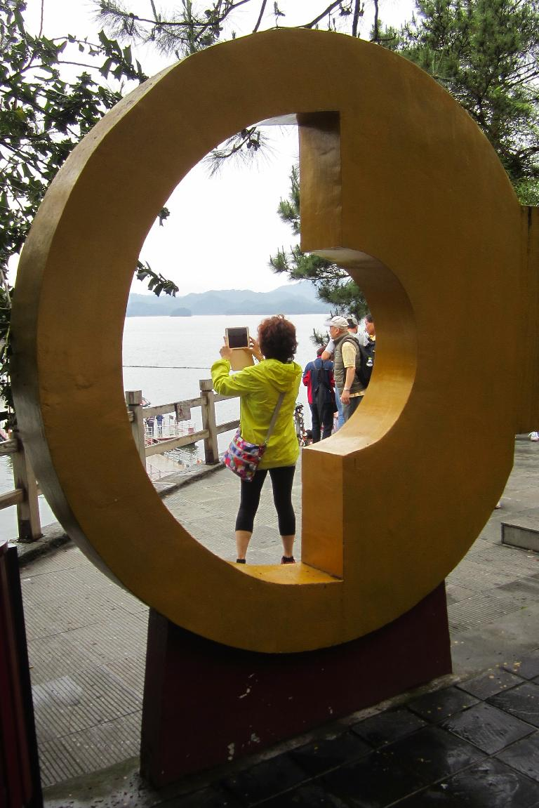 A giant key frames a tourist taking a photo.