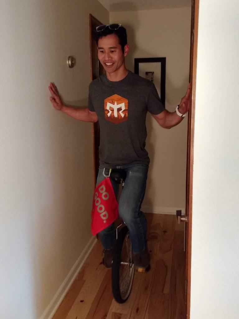 Felix Wong riding a unicycle... sort of.