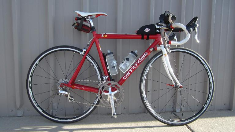 Red Cannondale 3.0 road bike, white saddle and fork, aerobars