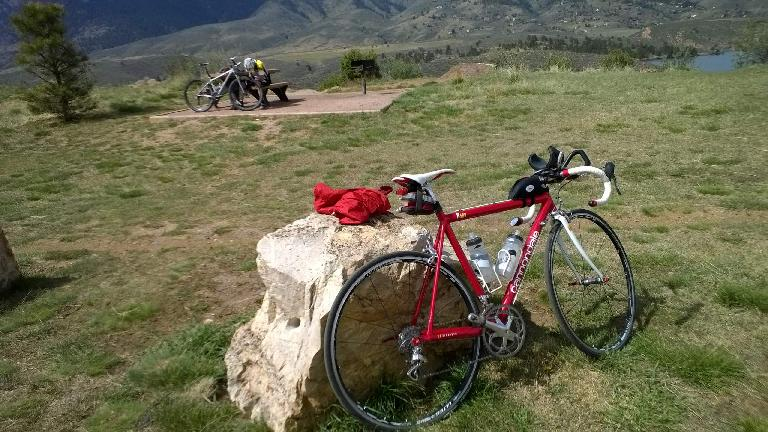 Person inflating mountain bike tire, red Cannondale 3.0, Fort Collins