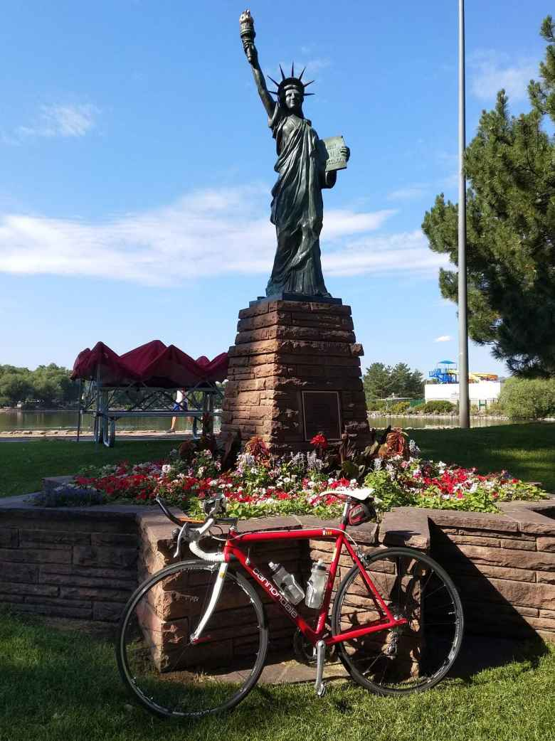 Red 1992 Cannondale R500 3.0 with white fork in front of the Statue of Liberty in Fort Collins' City Park.
