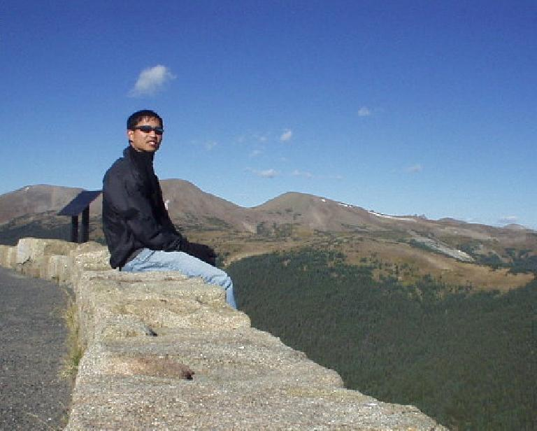Felix Wong enjoying the view of the Rockies and forests from afar.