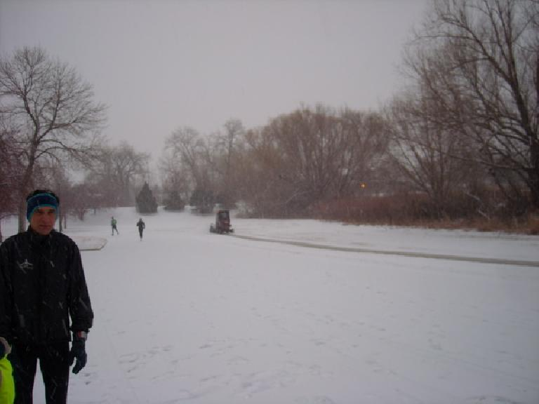 So much new snow!  A snowplow for clearing sidewalks clears a trail after several participants of the Rolland Moore Park 4k had already started running.