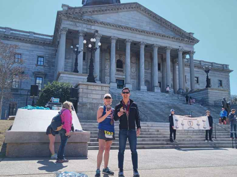 Mel Sirois and Felix Wong with their first-place age-group trophies at the 2020 Run Hard Columbia Marathon in front of the state capital.