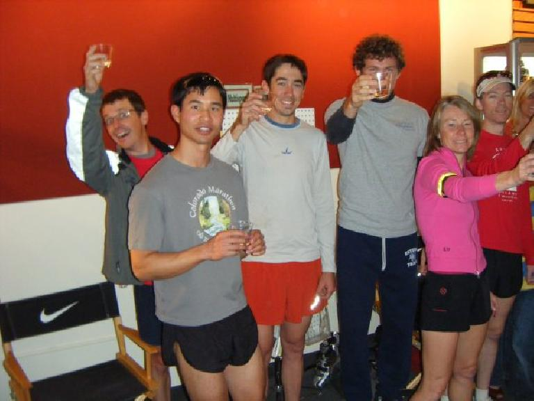 Scott Slusher, Felix Wong, man in white shirt, Tim Vail, Catherine Speights, Dan Jones holding up plastic cups for a cheers in the new Runners Roost