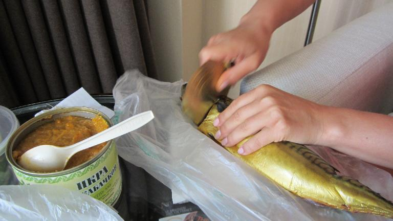 Katia, ever so resourceful, cuts the fried fish with the tin lid from the squash sauce.