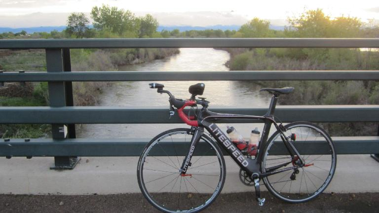 Black 2010 Litespeed Archon C2 on a bridge over a river looking towards the mountains, Windsor, Colorado