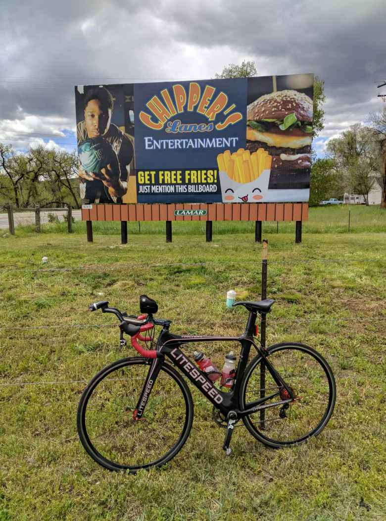 "Mile 101: ""Get free fries!"" My black Litespeed Archon C2 in front of a billboard for Chipper's Lanes in Loveland, Colorado."
