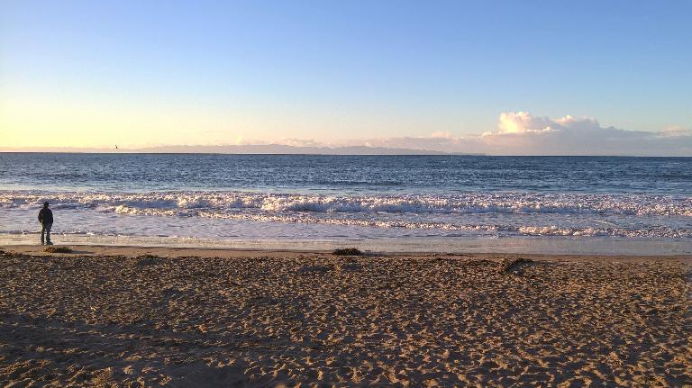 A man walks by the water at Arroyo Burro Beach in Santa Barbara.