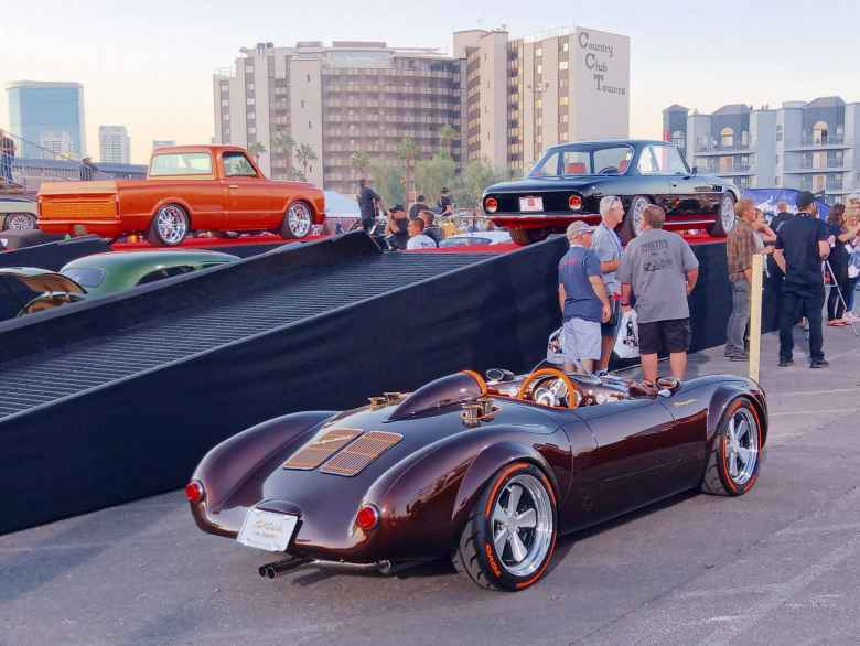 A Porsche 550 Spyder in merlot, with an orange truck and black coupe in the background.