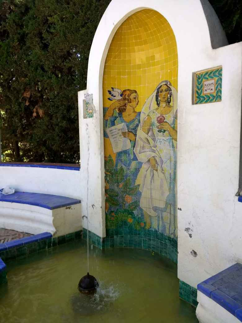 "A fountain with a mural labeled ""Manon"" in the Parque de Maria Luisa in Seville, Spain."
