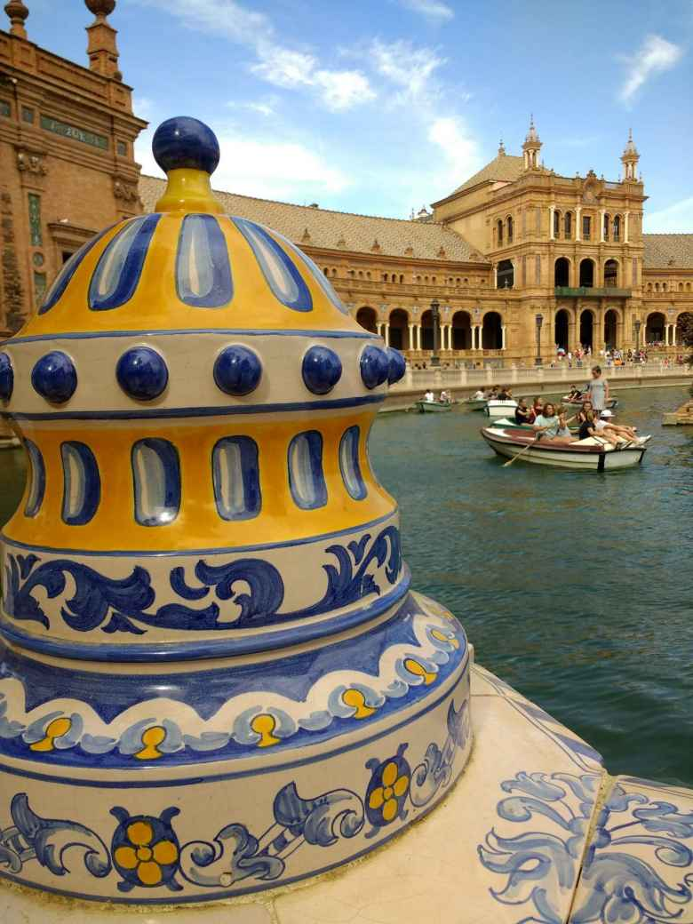 Blue, yellow, and white art sculpture, and canoes in the canal, by the Plaza de España in Seville, Spain.