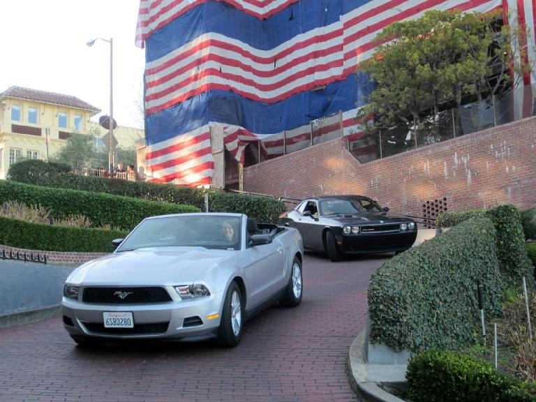 All-American scene: Kelly in a Ford Mustang being followed by a Dodge Challenger with the U.S. colors in the background on Lombard St.