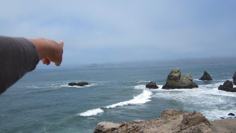 Pointing at a rock.