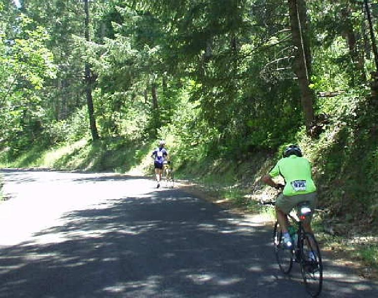 [Mile 81, 12:47 p.m.] AJ motors up Slug Gulch Rd. and is about to pass someone walking.  We saw at least two people walking up their bikes; it was that steep!