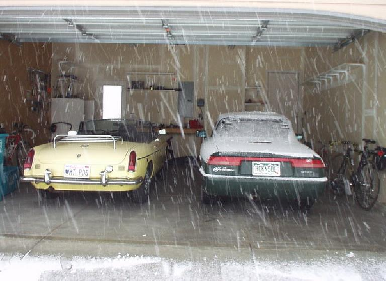 snow falling outside garage containing yellow 1969 MGB roadster and snow-covered green 1991 Alfa Romeo Spider Veloce