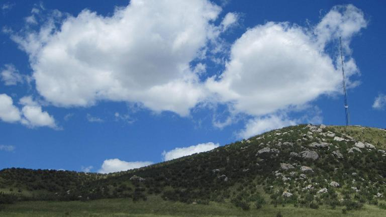 Clouds above the grassy hills.