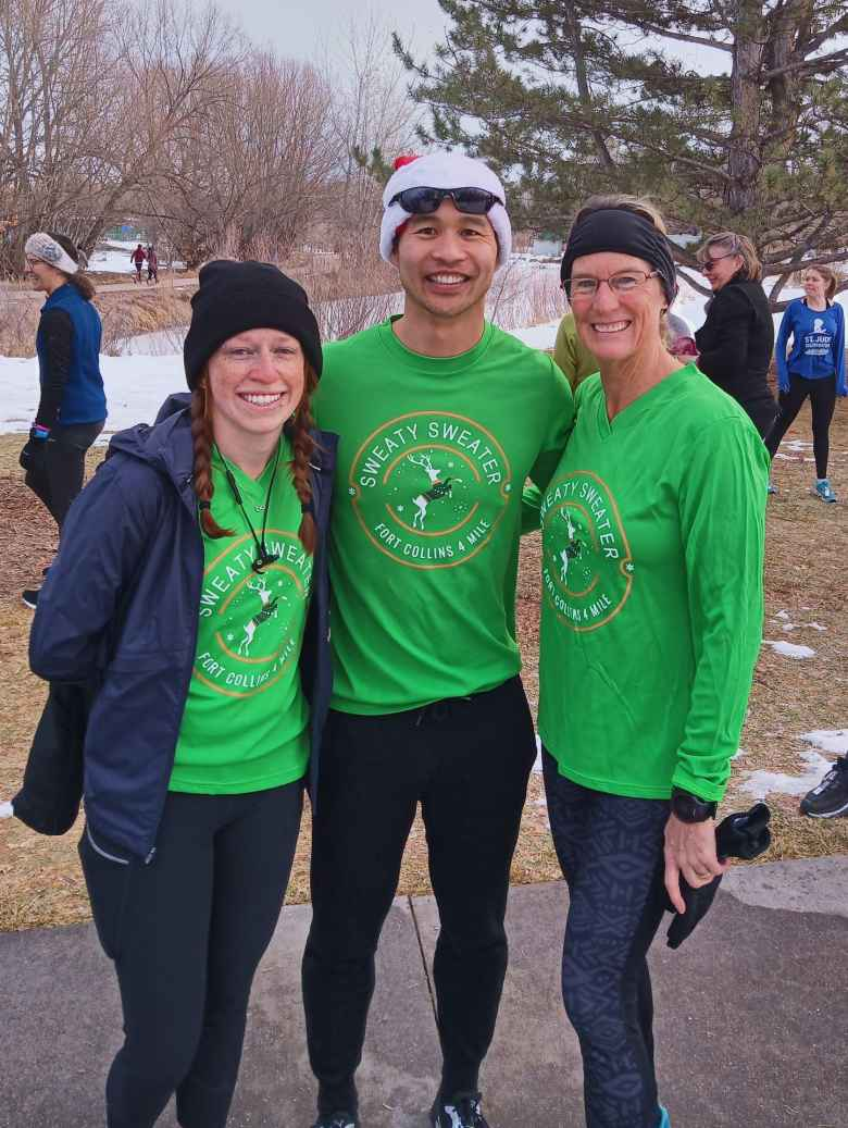 Brooke, Felix, and Cathy wearing green Sweaty Sweater 4 Mile shirts from the race they ran the day before.